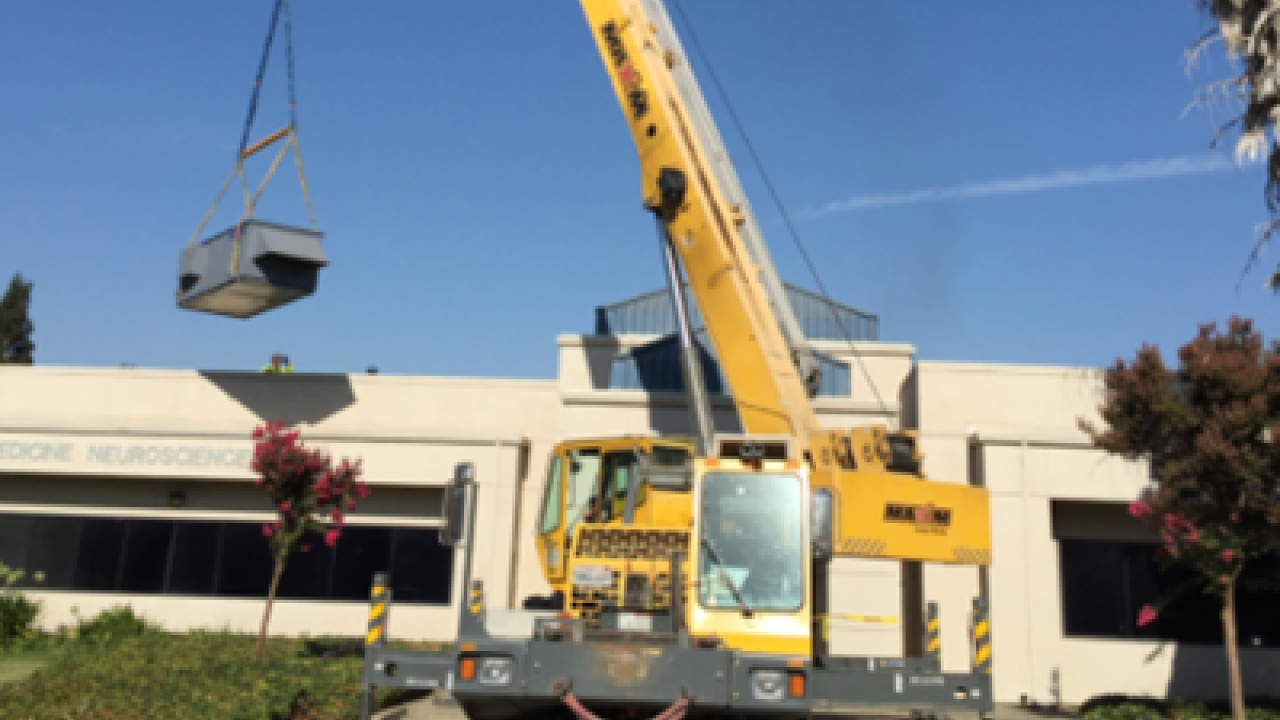 Photo of a crane lifting an air handler.