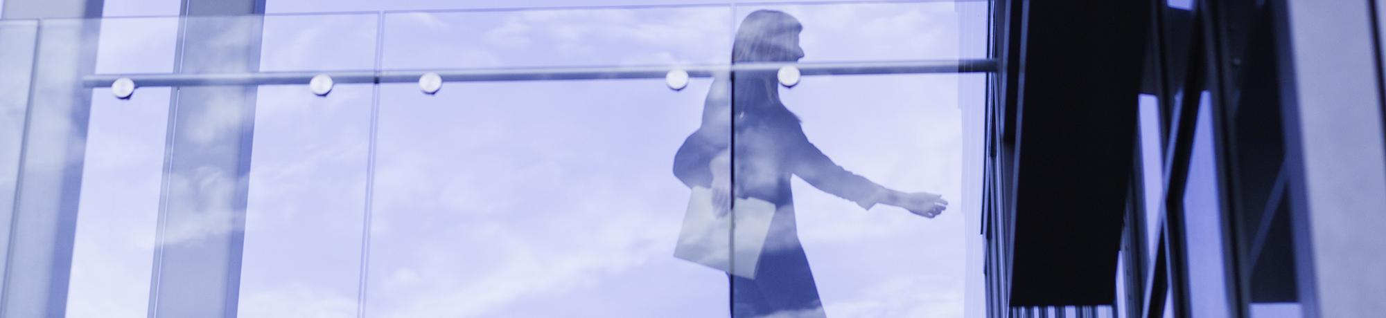 Decorative image of person walking across skybridge.